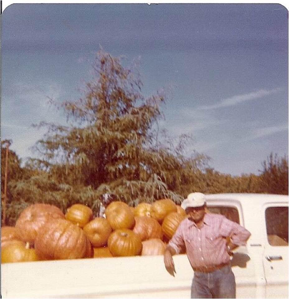 old photo of man standing next to pickup truck full of pumpkins