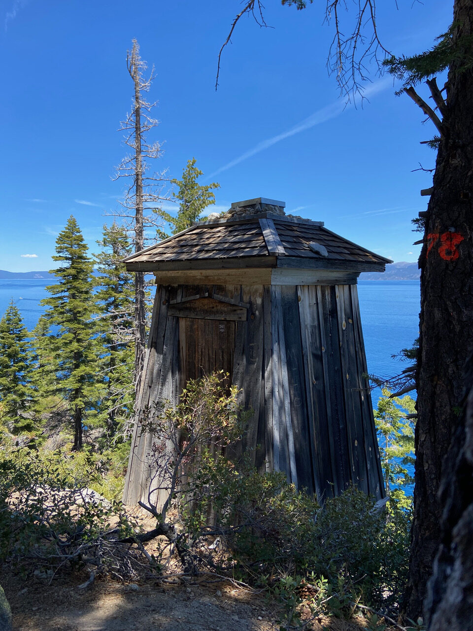old wooden lighthouse building along hiking trail