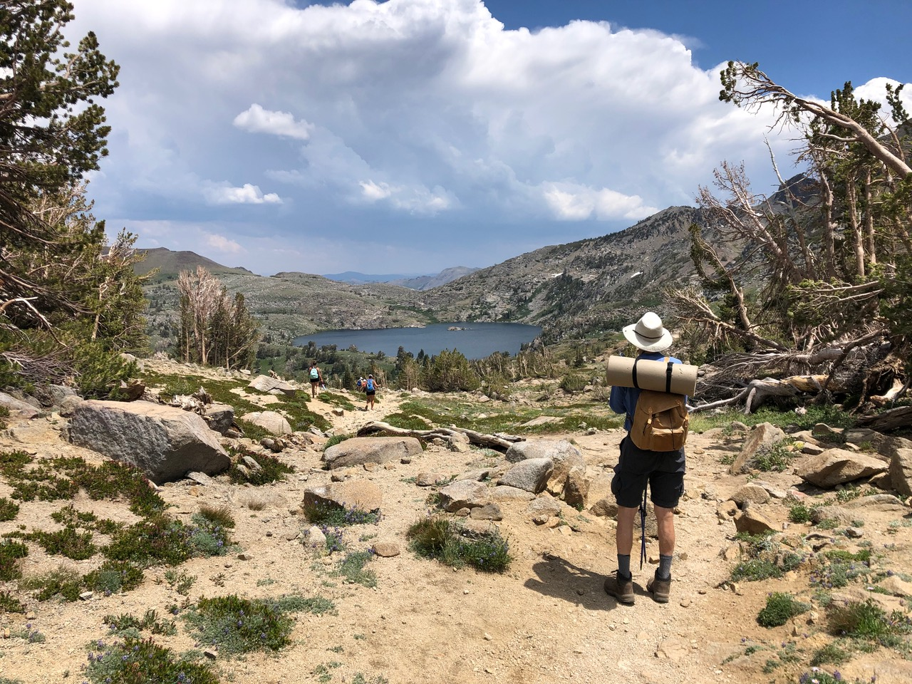 person hiking trail overlooking a lake