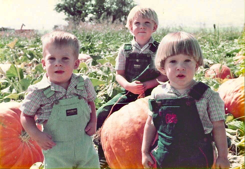 old photo of three children sitting in pumpkin patch