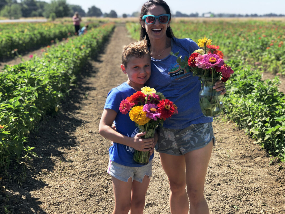 mother and son standing in a flower field each holding a bouquet of flowers