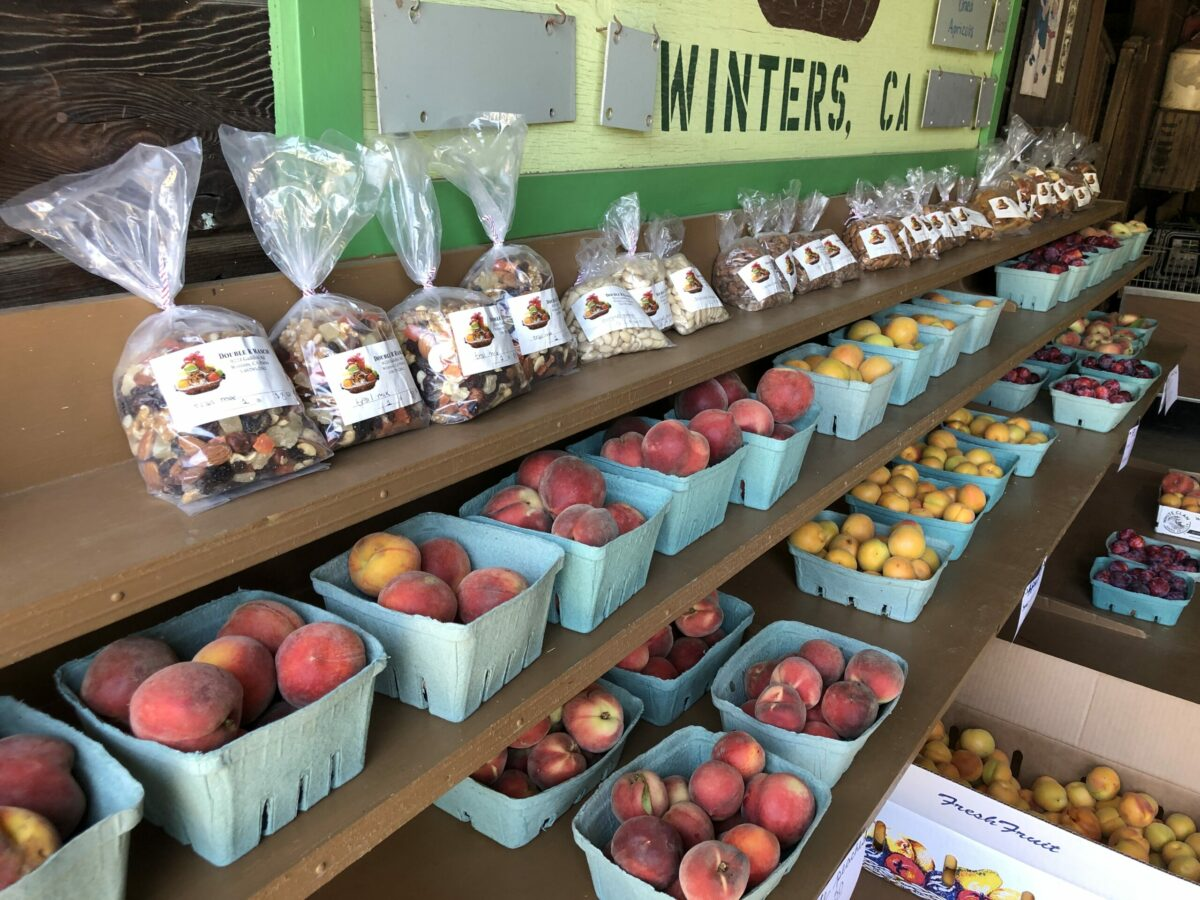 boxes of white peaches and trailmix at farmers market