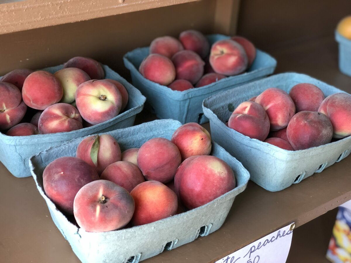 boxes of white peaches at farmers market