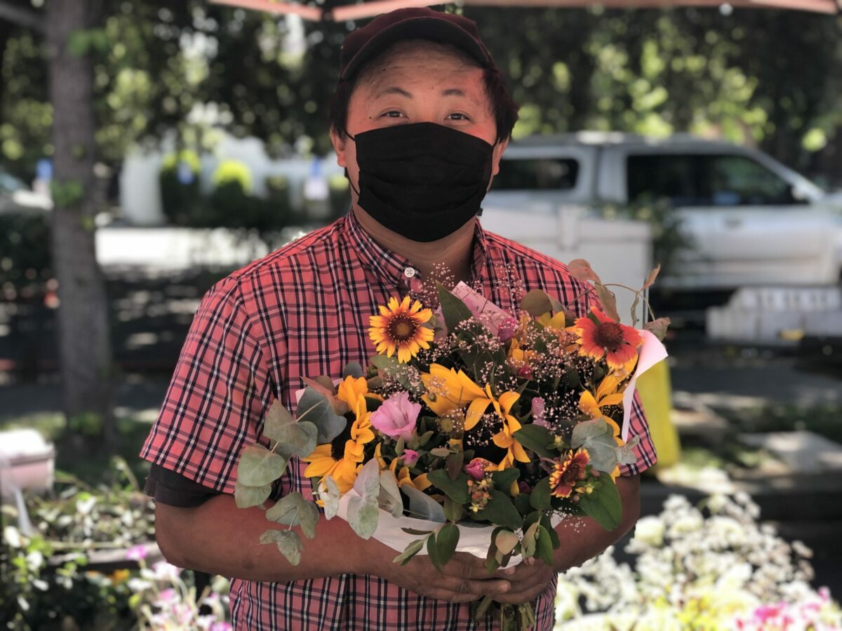 man holding bouquet of flowers at farmers market