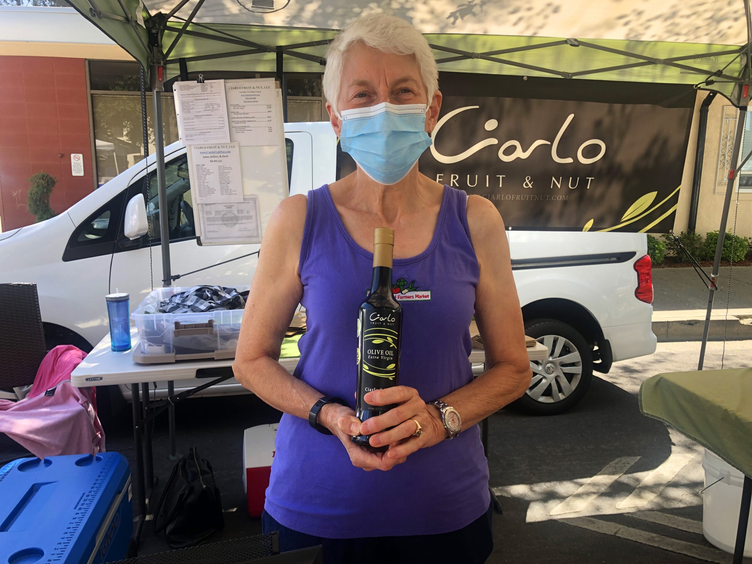 Patricia Calvert holding a bottle of olive oil at Woodland Farmers Market